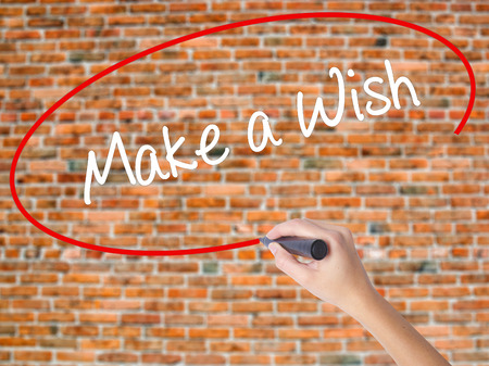 Woman Hand Writing Make a Wish  with black marker on visual screen. Isolated on bricks. Business concept. Stock Photo