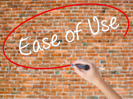 Woman Hand Writing Ease of Use with black marker on visual screen. Isolated on bricks. Business, technology, internet concept. Stock Photo
