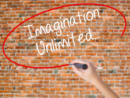 Woman Hand Writing Imagination Unlimited... with black marker on visual screen. Isolated on bricks. Business concept. Stock Photo