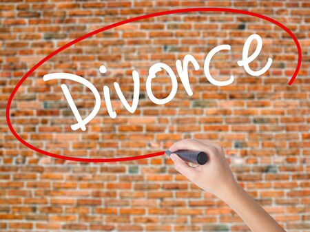 Woman Hand Writing Divorce  with black marker on visual screen. Isolated on bricks. Business concept. Stock Photo