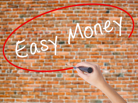 Woman Hand Writing Easy Money with black marker on visual screen. Isolated on bricks. Business concept. Stock Photo Stock Photo