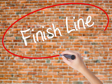 Woman Hand Writing Finish Line with black marker on visual screen. Isolated on bricks. Business, technology, internet concept. Stock fotó
