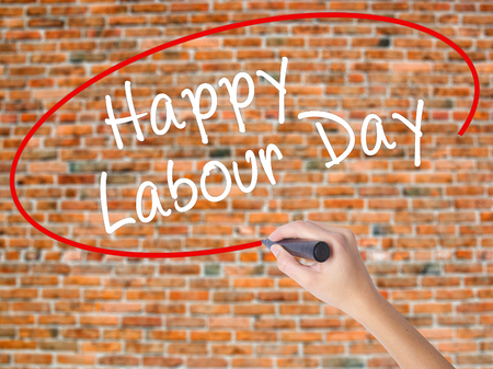 Woman Hand Writing Happy Labor Day with black marker on visual screen. Isolated on bricks. Business concept. Stock Photo