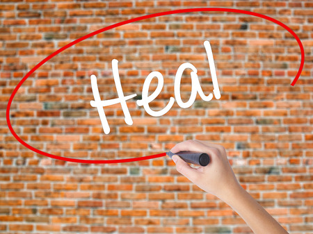 Woman Hand Writing  Heal  with black marker on visual screen. Isolated on bricks. Business concept. Stock Photo