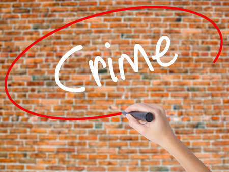 handcuffs: Woman Hand Writing Crime with black marker on visual screen. Isolated on bricks. Business concept. Stock Photo Stock Photo