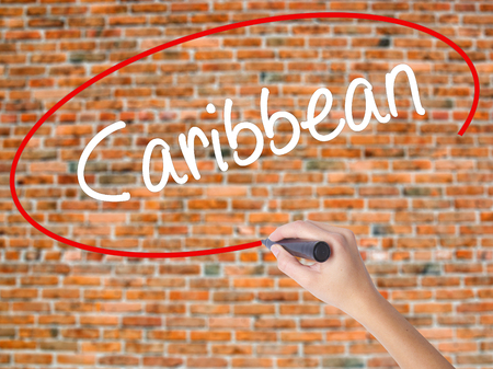 Woman Hand Writing Caribbean with black marker on visual screen. Isolated on bricks. Business concept. Stock Photo Stock Photo