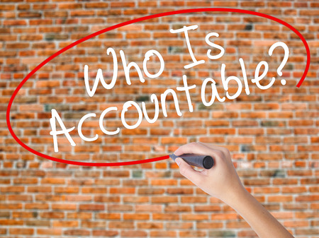 Woman Hand Writing Who Is Accountable? with black marker on visual screen. Isolated on bricks. Business concept. Stock Photo