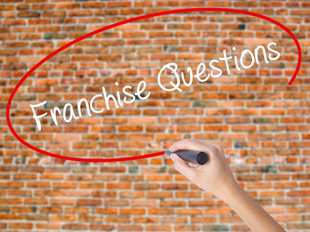 Woman Hand Writing Franchise Questions with black marker on visual screen. Isolated on bricks. Business concept. Stock Photo Stock Photo