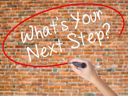 Woman Hand Writing Whats Your Next Step? with black marker on visual screen. Isolated on bricks. Travel technology, internet concept. Stock Image