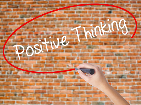 Woman Hand Writing Positive Thinking with black marker on visual screen. Isolated on bricks. Business concept. Stock Photo