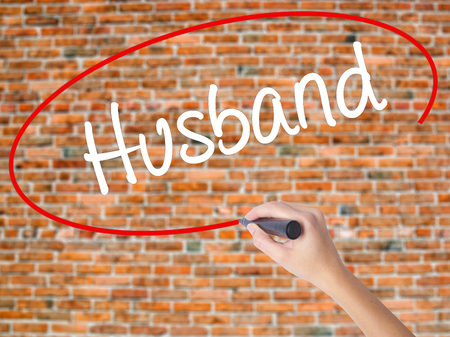 Woman Hand Writing Husband with black marker on visual screen. Isolated on bricks. Business concept. Stock Photo