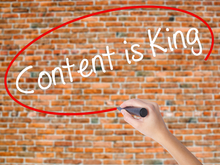 Woman Hand Writing Content is King with black marker on visual screen. Isolated on bricks. Business concept. Stock Photo