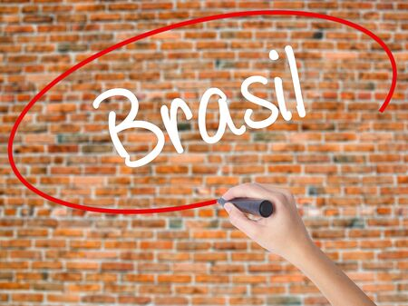 Woman Hand Writing Brasil ( Brazil  in Portuguese) with black marker on visual screen. Isolated on bricks. Business, technology, internet concept.