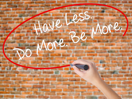 Woman Hand Writing Have Less. Do More. Be More.  with black marker on visual screen. Isolated on bricks. Business concept. Stock Photo