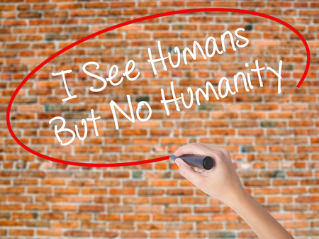Woman Hand Writing I See Humans But No Humanity with black marker on visual screen. Isolated on bricks. Business, technology, internet concept. Stock  Photo