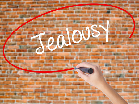 Woman Hand Writing Jealousy with black marker on visual screen. Isolated on bricks. Business concept. Stock Photo Foto de archivo