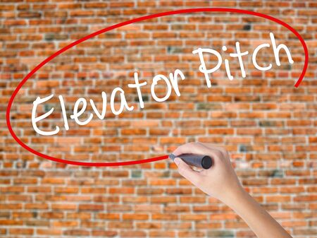business pitch: Woman Hand Writing Elevator Pitch with black marker on visual screen. Isolated on bricks. Business concept. Stock Photo
