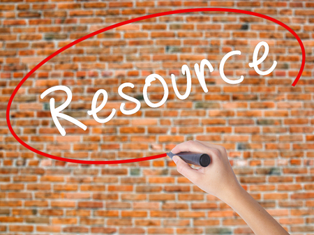 Woman Hand Writing Resource with black marker on visual screen. Isolated on bricks. Business concept. Stock Photo
