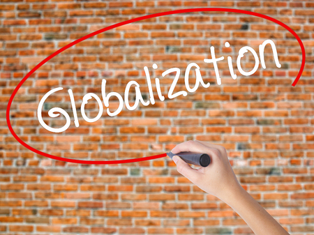 Woman Hand Writing Globalization with black marker on visual screen. Isolated on bricks. Business concept. Stock Photo