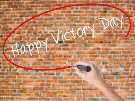 Woman Hand Writing Happy Victory Day with black marker on visual screen. Isolated on bricks. Business, technology, internet concept. Stock  Photo