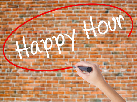 happyhour: Woman Hand Writing Happy Hour with black marker on visual screen. Isolated on bricks. Business concept. Stock Photo