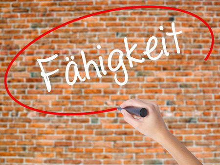 Woman Hand Writing Fahigkeit (Ability in German) with black marker on visual screen. Isolated on bricks. Business concept. Stock Photo