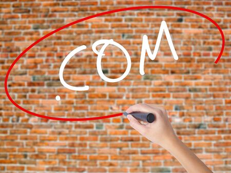 Woman Hand Writing .COM with black marker on visual screen. Isolated on bricks. Business concept. Stock Photo