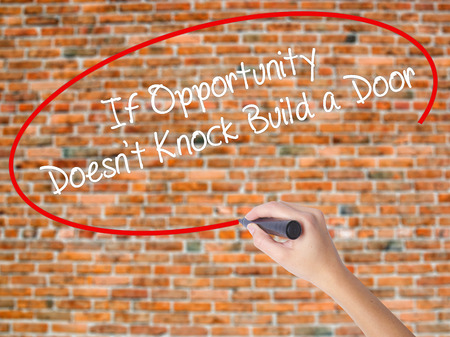Woman Hand Writing If Opportunity Doesnt Knock Build a Door with black marker on visual screen. Isolated on bricks. Business concept. Stock Photo