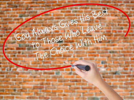 Woman Hand Writing God Always Gives His Best to Those Who Leave The Choice With Him with black marker on visual screen. Isolated on bricks. Business concept. Stock Photo