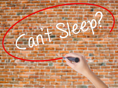 molesto: ¿Escritura de la mano de la mujer que no puede dormir? con el marcador negro en la pantalla visual. Aislado en ladrillos. Concepto de negocio. Foto de stock