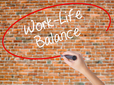 health equity: Woman Hand Writing Work-Life Balance with black marker on visual screen. Isolated on bricks. Business concept. Stock Photo Stock Photo