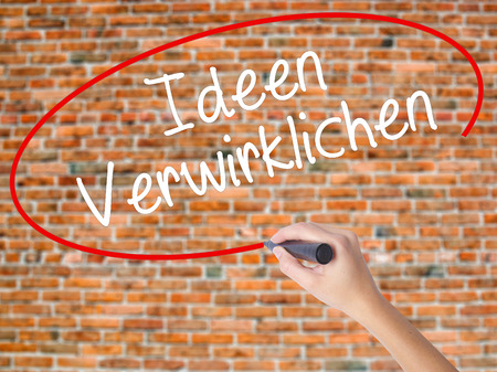 revelation: Woman Hand Writing Ideen Verwirklichen ( Realize Ideas in German) with black marker on visual screen. Isolated on bricks. Business concept. Stock Photo