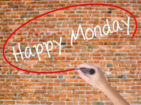 Woman Hand Writing Happy Monday with black marker on visual screen. Isolated on bricks. Business concept. Stock Photo
