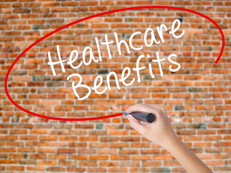 Woman Hand Writing Healthcare Benefits with black marker on visual screen. Isolated on bricks. Business concept. Stock Photo