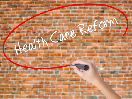 Woman Hand Writing Health Care Reform with black marker on visual screen. Isolated on bricks. Business, technology, internet concept.