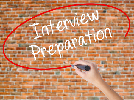 Woman Hand Writing Interview Preparation with black marker on visual screen. Isolated on bricks. Business concept. Stock Photo