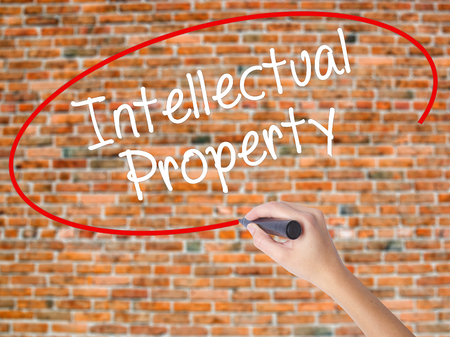lawer: Woman Hand Writing Intellectual Property with black marker on visual screen. Isolated on bricks. Business concept. Stock Photo