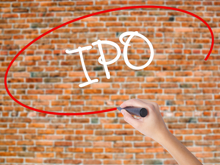 insider: Woman Hand Writing IPO (Initial Public Offering)   with black marker on visual screen. Isolated on bricks. Business concept. Stock Photo Stock Photo