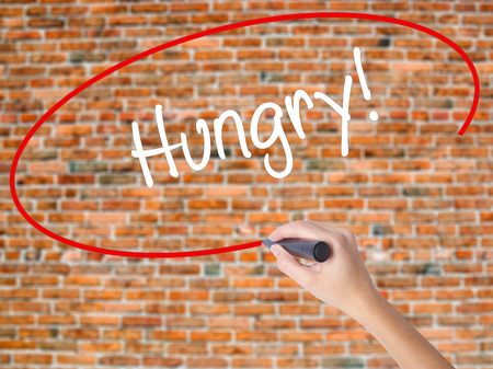 Woman Hand Writing Hungry! with black marker on visual screen. Isolated on bricks. Business concept. Stock Photo Stock Photo