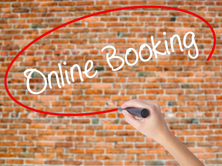 Woman Hand Writing  Online Booking  with black marker on visual screen. Isolated on bricks. Business concept. Stock Photo Stock Photo