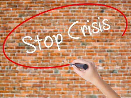 Woman Hand Writing Stop Crisis with black marker on visual screen. Isolated on bricks. Business concept. Stock Photo