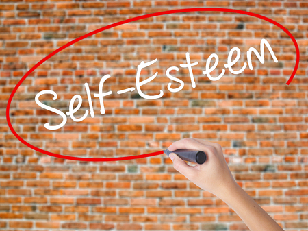 Woman Hand Writing Self-Esteem with black marker on visual screen. Isolated on bricks. Business concept. Stock Photo