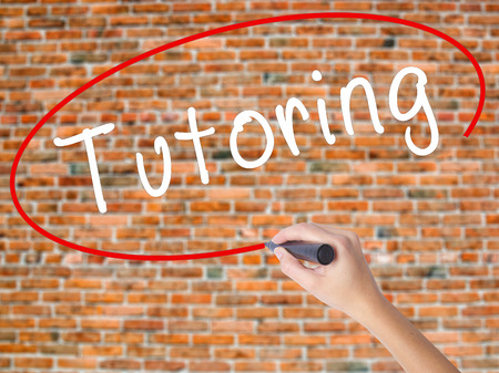 Woman Hand Writing Tutoring with black marker on visual screen. Isolated on bricks. Business concept. Stock Photo