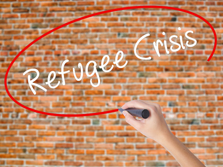 Woman Hand Writing Refugee Crisis with black marker on visual screen. Isolated on bricks. Business concept. Stock Photo