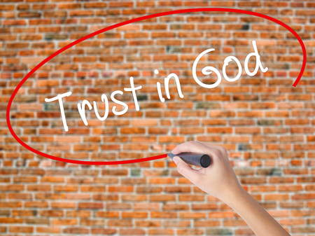 Woman Hand Writing Trust in God with black marker on visual screen. Isolated on bricks. Business concept. Stock Photo