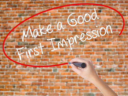 Woman Hand Writing Make a Good First Impression with black marker on visual screen. Isolated on bricks. Business concept. Stock Photo