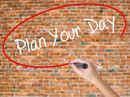 Woman Hand Writing Plan Your Day with black marker on visual screen. Isolated on bricks. Business concept. Stock Photo