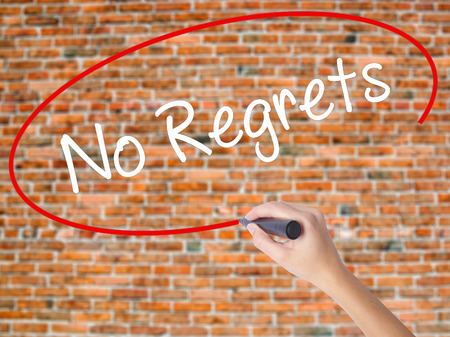 Woman Hand Writing No Regrets with black marker on visual screen. Isolated on bricks. Business concept. Stock Photo Stock Photo
