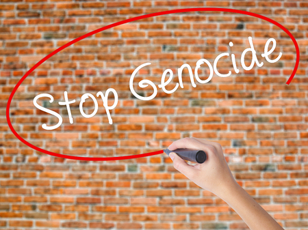Woman Hand Writing Stop Genocide with black marker on visual screen. Isolated on bricks. Business concept. Stock Photo
