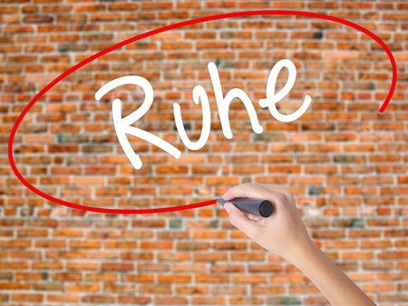 Woman Hand Writing Ruhe (Quiet in German) with black marker on visual screen. Isolated on bricks. Business concept. Stock Photo